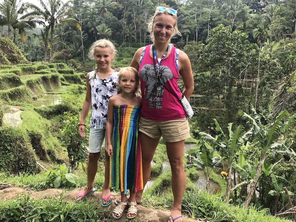 Mutter mit zwei Töchtern in Ubud in Bali vor Reisfeldern.