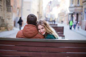 Ein Pärchen sitzt mit dem Rücken zur Kamera aneinandergekuschelt auf einer Parkbank in einer Fussgängerzone. Er blickt geradeaus. Sie hat die Wange an seiner Schulter und dreht dabei den Kopf zur Kamera. Sie lächelt glücklich und strahlt.